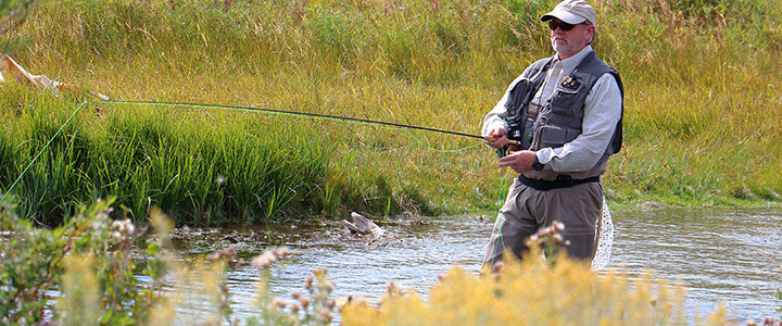 man fly fishing in waders